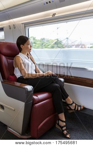 Business class in train. Asian lady enjoying view in train commute. Woman enjoying view during morning commute. Businesswoman relaxing looking out the window in travel transport.