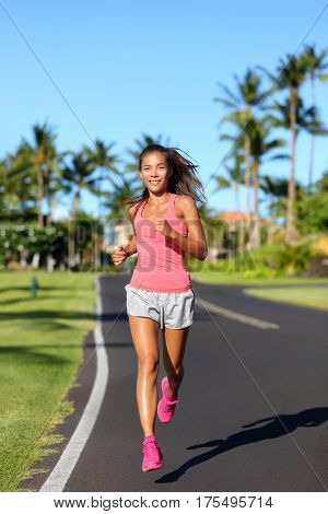 Healthy Asian woman runner jogging on urban road. Fitness girl athlete working out living an active lifestyle training cardio in the morning running in pink activewear. Full body.