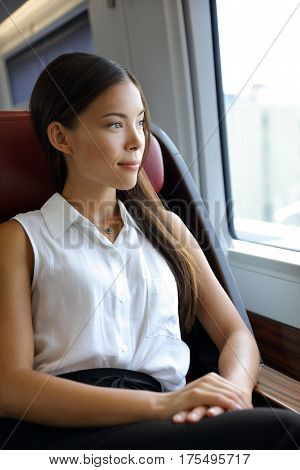 Beautiful Asian young professional woman enjoying view on travel commute. Business class by train. Businesswoman relaxing in luxury high end seat in transport.