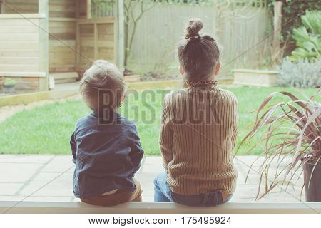 Two Little Girls Sitting On The Floor Looking At The Garden