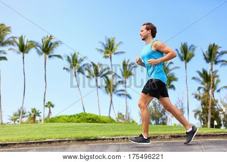 Fitness man athlete runner jogging on park sidewalk. Person running working out living an active lifestyle training cardio in summer in sportswear and shoes. Full body.