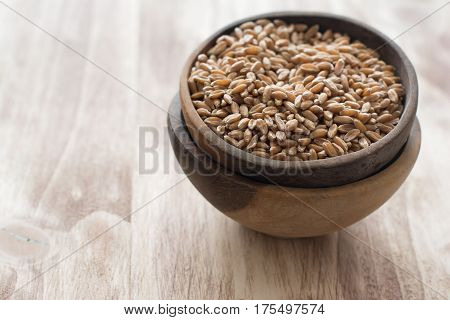 Uncooked spelt in the wooden bowl selective focus