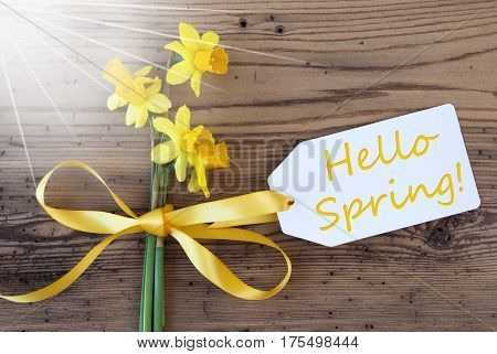 Label With English Text Hello Spring. Sunny Yellow Spring Narcissus Or Daffodil With Ribbon. Aged, Rustic Wodden Background. Greeting Card For Spring Season