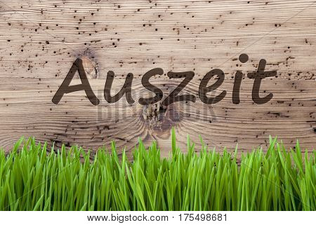 German Text Auszeit Means Downtime. Spring Season Greeting Card. Bright Aged Wooden Background With Gras.