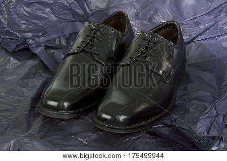 Black Mens shoes on crumbled black Paper