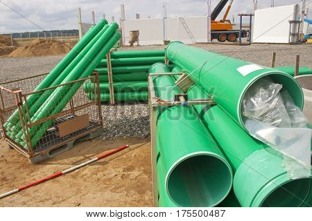 Stack of green sewer pipes on building site outdoor shot