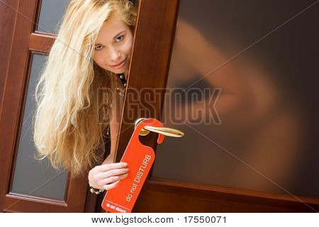"Sexy woman smiling, looking from behind the door, holding hotel sign ""do not disturb"""