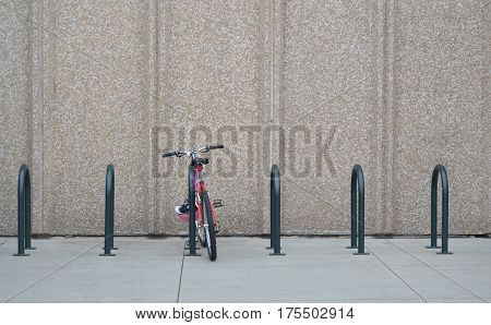 Red bike parked in bike rack in front of concrete wall