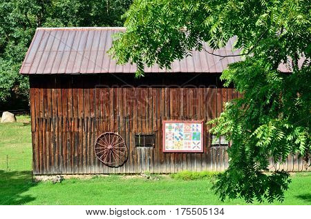 Barn quilt and wagon wheel decorate an old barn