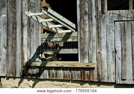Ladder creates a shadow below a barn window