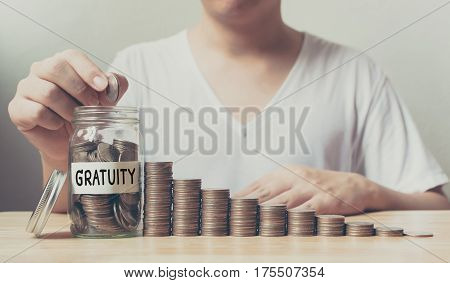 Hand putting coins in jar word gratuity with money stack step growing growth saving money Concept finance business investment