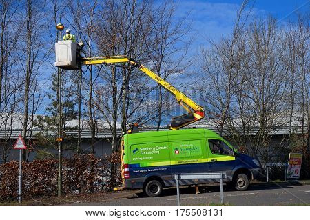 Basingstoke UK - March 9th 2017: Electrician on a cherry picker elevated platform maintains a street light working for Southern Electric Contracting and Hampshire County Council