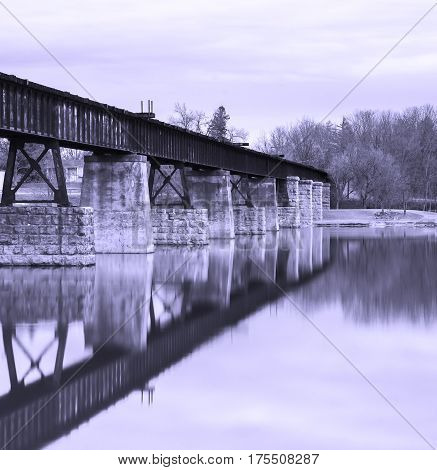 Railway bridge over still waters reflection of track and stone pillars dividing the image