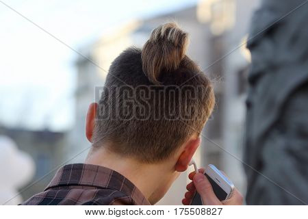 young guy inserts headphones in ear holding a mobile phone