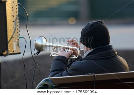 the a street musician plays the trumpet