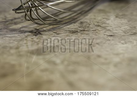 Closeup of metal wisk on marbled kitchen counter background with space for text
