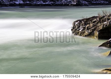 Smooth aquamarine current of strong river flowing through rocky riverbank with snow