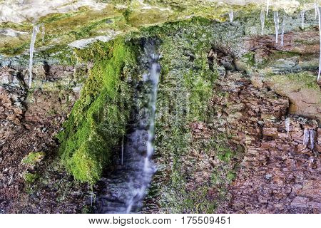 Water trickling from red rock face under overhang green moss growing in micro environment