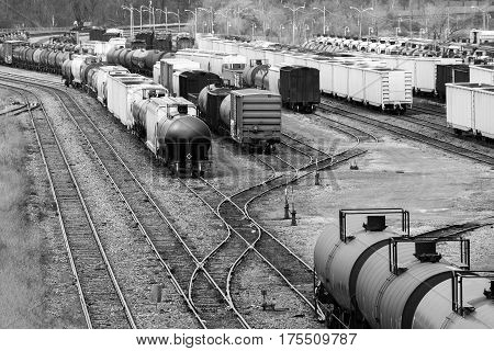 Many boxcars and cargo shipping train cars on tracks in a busy trainyard in black and white