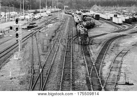 Busy trainyard with many trains on multiple switching tracks in black and white