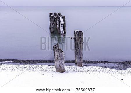 Broken pier with two posts on the shore disconnected from the remaining ruins in the calm tranquil water