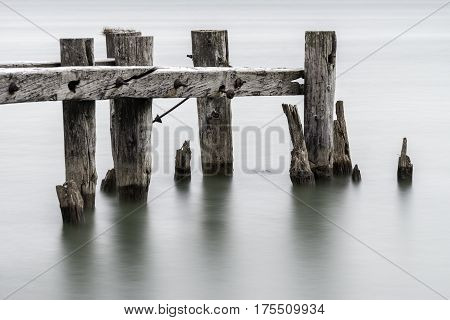 End of an old broken pier closeup of posts standing in calm tranquil water