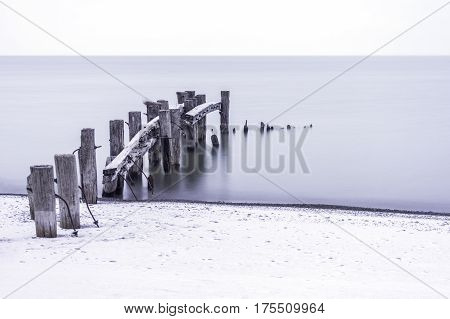 Old broken pier with rustic and weathered posts leading into a calm tranquil sea winter scene