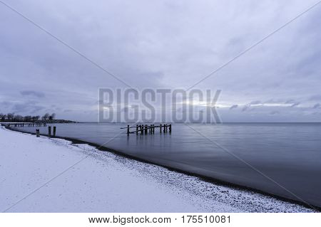 Winter shoreline with broken pier posts standing in tranquil sea water snow on beach blue sky