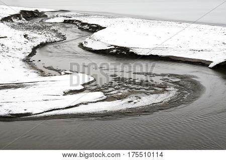 Flowing winding stream cutting a path to the sea through a winter beach tranquil scene