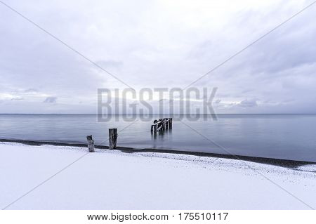 Tranquil sea with broken pier posts leading into the water snow on winter beach