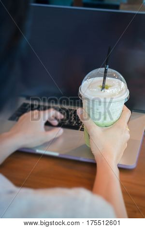 Woman Hand On Iced Milk Green Tea During Typing stock photo