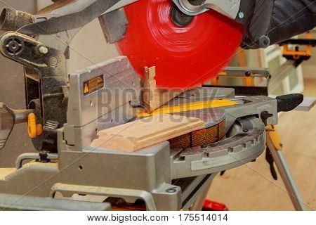 man cutting wood on electric saw saw for cutting wood flooring