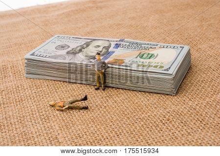 Men Figurines Beside The Bundle Of Us Dollar Banknote