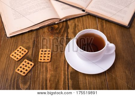 Hot cup of tea on wooden table with biscuit cookies and books : top view - tea time.