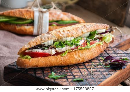 Long Baguette Sandwich With Lettuce Tomatoes Eggs Onion And Mayo Sauce Served On A Wooden Board. Rus