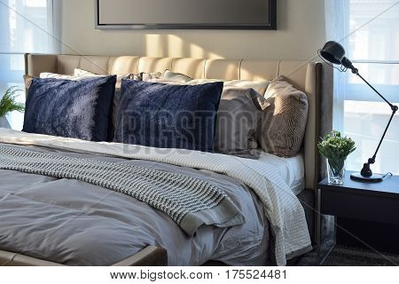 Modern Bedroom With Blue Pillows And Black Lamp On Table