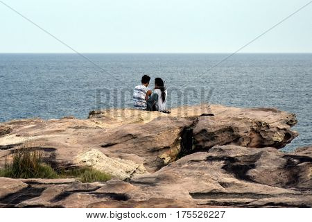 Young asian couple sitting on the rock at Shark Point. Couple enjoying Tasman sea view before sunset. The rock is named after its shape, shark face.