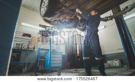 Car service - a mechanic checks the suspension of car, wide angle, horizontal