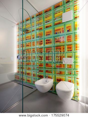 Modern bathroom, toilet and bidet and colored tiles on the wall