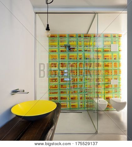Luxury apartment, modern bathroom with yellow sink, shower and colored tiles