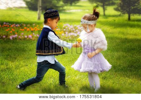kazakh little boy and girl together playing in the summer park