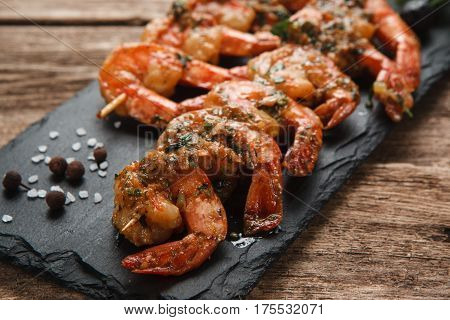 Japanese seafood. Fried spicy shrimps with herbs on wooden skewers served on black slate, close up view.