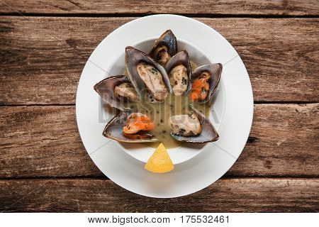 Appetizing clams served with cream sauce on white round plate decorated with lemon. Background of rustic wooden table, flat lay. Luxury restaurant menu photo.