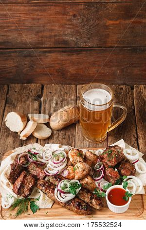 Appetizing meal in pub with fresh grilled meat assortment, pita bread, buns, and mug of cold light beer served on rustic wooden background, free space