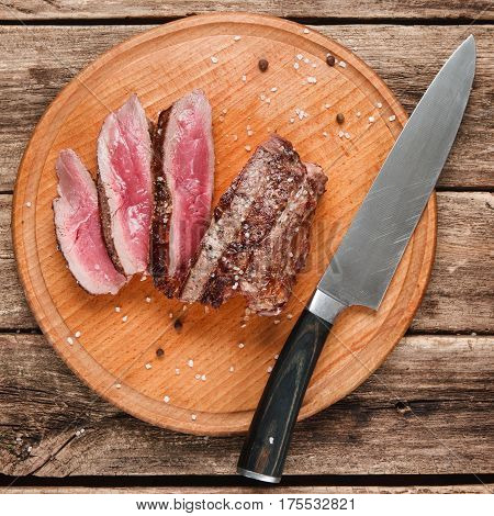 Slices of superior grilled meat served on round platter with big knife, on rustic wooden table, close up view. Menu photo.