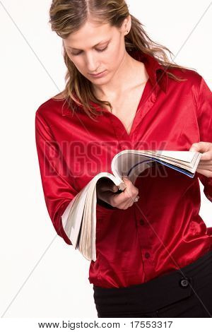Attractive young woman in red shirt reading magazine