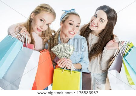 Smiling young women holding shopping bags and dollar banknotes