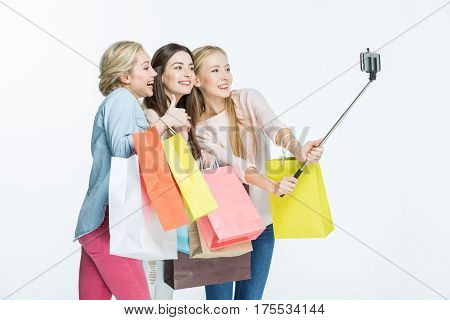 Three young women holding shopping bags and making selfie on smartphone