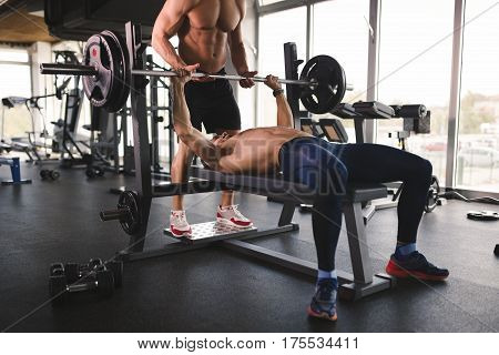People bench pressing in gym and working out