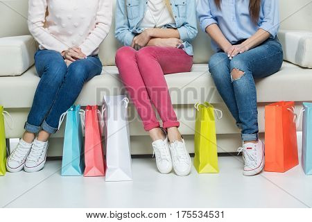 Partial view of young women sitting on sofa with shopping bags